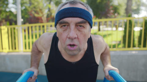 A retired elderly man works out on a sports ground outside. Healthy lifestyle Live Action