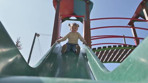 Little blond girl sliding the slide at children's playground Live Action