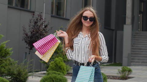 Teenager girl in trendy clothes with multicolor shopping bags. Black Friday sale Live Action