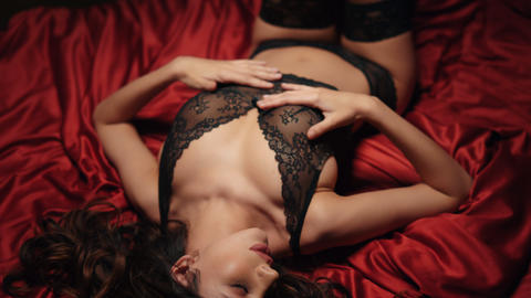 Sexy girl pleasuring herself on red silk sheets. Closed eyes woman stroking body Live Action