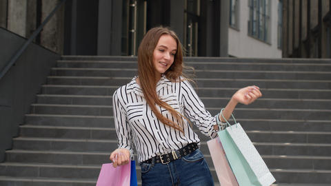 Stylish girl holding shopping bags and showing OK sign. Rejoicing with good Live Action