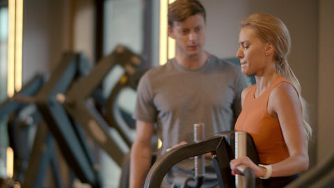 Sexy fit couple training at gym. Sport woman making bicep curls in sport club Live Action