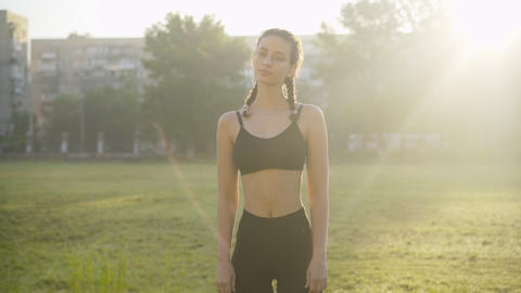Young slim Caucasian woman warming up at sunrise outdoors. Portrait of confident Live Action