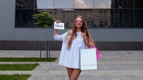 Young stylish girl showing Sale word inscription text, smiling, looking Live Action