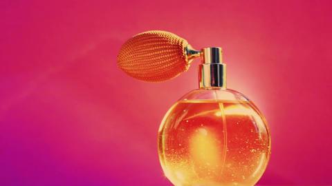 Golden fragrance bottle and shining light flares on pink background, glamorous Live Action