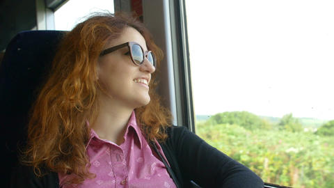 young smiling woman traveling on the train looking out the window Footage