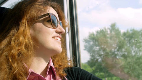 relaxed young woman on the train smiling near the window seat Footage