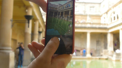 young woman making photos with a smartphone inside a museum, archeological area Footage