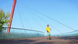 Child cruising down a bridge on a pennyboard, slow motion Footage