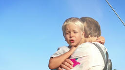 Little boy in mothers arms, beautiful lens flare, slow motion Footage