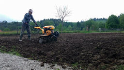 Man plowing field with cultivator, spring garden preparation Footage