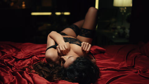 Passionate girl touching breasts red silk bed. Horny woman fantasizing bedroom Live Action