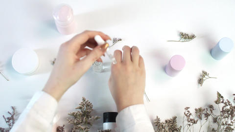 Woman applying hand serum on her hands. Beauty theme flat lay creative layout Live Action