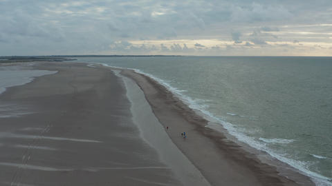 Family walking together over Sand Beach on Cloudy Day, Aerial Tilt down Live Action