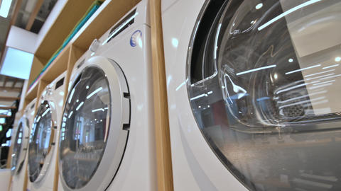 rows of washing machines and dryers in domestic appliances store Live Action