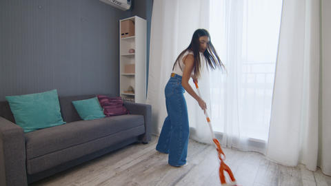 Cheerful woman cleaning the house while singing using mop as microphone Live Action