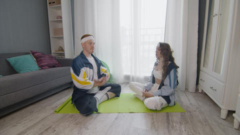 Young fit family sitting on the floor, meditating together, keeping a healthy Live Action