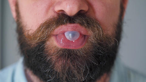 Bearded man chewing bubble gum. Man blowing out a bubble of chewing gum Live Action