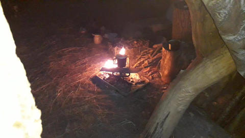 Tea is brewed over a fire in a forest tent Live Action