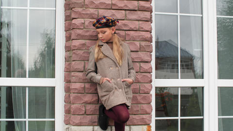 Fashion teen girl in autumn coat and beret leaning on brick house wall. Stylish Live Action