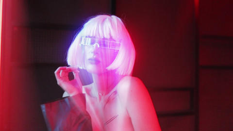 Neon pink projection of a woman in futuristic glasses. Neon noir Live Action