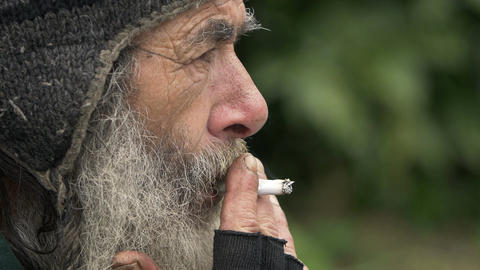 old man smoking: side view of an homeless lonely in the city Footage