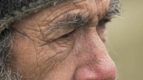 very old man smoking in the street: eyes of elderly man Footage