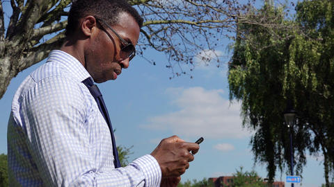 Businessman at the park using cell phone; mobile phone; smartphone Footage