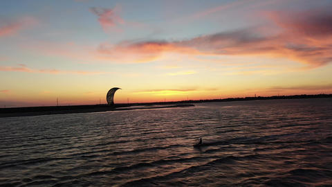 Stunning colorful sky during sunset and a kitesurfer gliding on the water, 4k ライブ動画