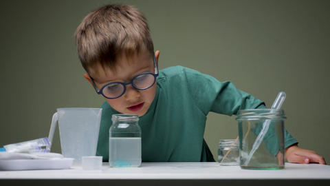 Boy in glasses does chemical experiment with pipette and liquid indoor. Studying Live Action