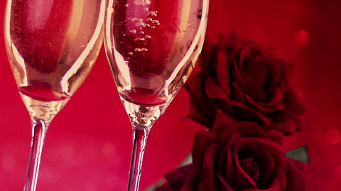 pouring champagne flutes with bubbles near red roses on red bokeh background, love and Live Action