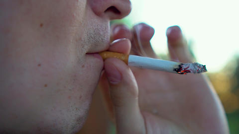 Close up of a young man smoking a cigarette. Bad smoking habit with health risks Live Action