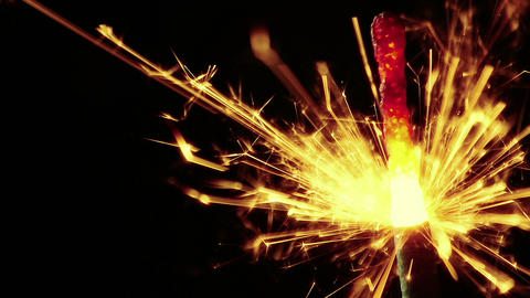 man lights up sparkler fireworks burning on a black background, congratulations, greetings, party, 실사 촬영