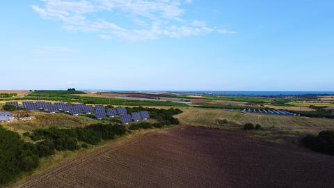 Agricultural fields for planting and solar panels station on field for alternative energy. Aerial Live Action