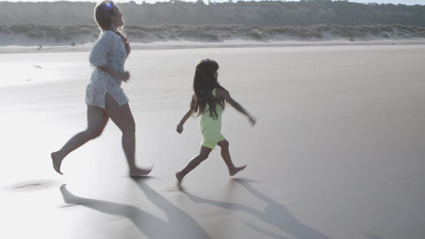 Little girl and her mom running on ocean beach Acción en vivo