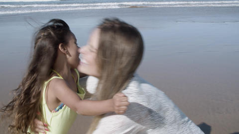 Sweet girl running on beach to her happy mom Acción en vivo