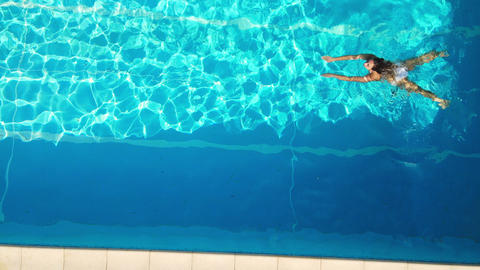 Young woman enjoys swimming in the cool water of a pool in summertime Acción en vivo