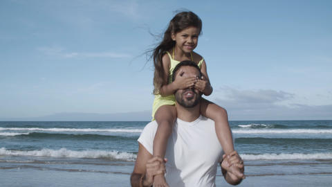 Joyful little girl riding on dads neck Acción en vivo