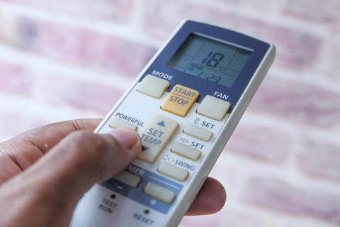 Close up of man hand holding air condition remote Photo