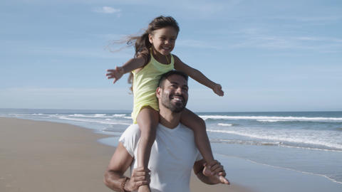 Joyful excited little girl riding on dads neck Acción en vivo
