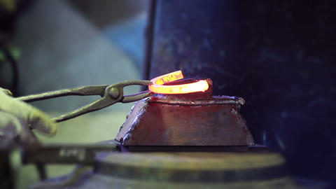 Blacksmith forges a hot horseshoe Footage