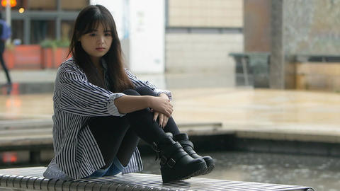 young sad girl sitting alone while rain falls behind: depressed asian woman Footage