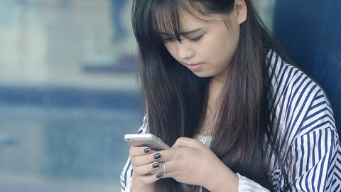 young chinese girl texting messages on the cell phone ビデオ