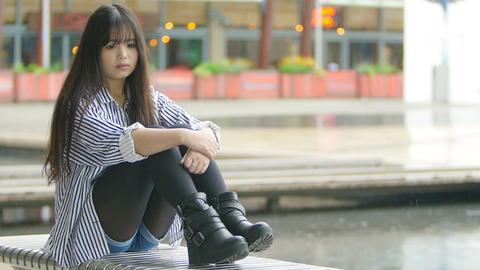 depressed and sad chinese woman sitting alone with rain in background Footage