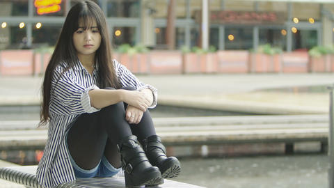 sad chinese young adult woman sitting alone on a bench in the city Footage