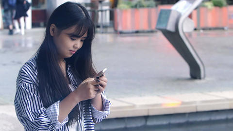 young asian woman composing messages with a cell phone:... Stock Video Footage
