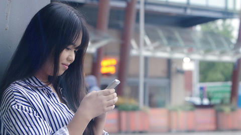 young chinese woman texting a message on the mobile phone ビデオ
