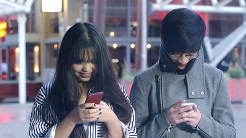 chinese people using smartphones with city lights in background Footage