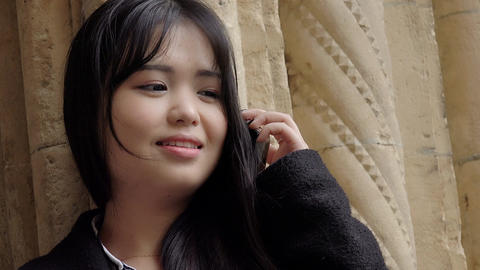 smiling young asian woman using a mobile phone: cell… Stock Video Footage