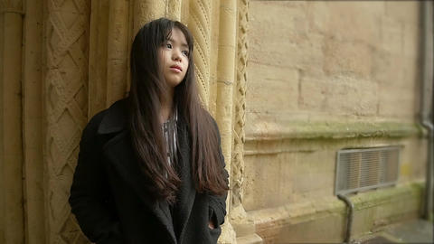 pensive and depressed lonely asian woman standing alone against a wall Footage